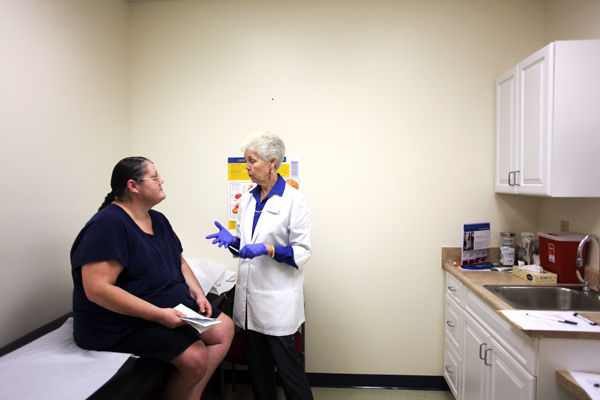 Volunteer nurse Shirley Baldwin (right) speaks to patient Vickie Quimby in an examination room during a visit to the Moore Free Care Clinic in Southern Pines, NC. The clinic depends on many volunteers like Baldwin, who volunteers there 1-2 days a week. (Photo by Ricky Leung / NC Policy Watch)
