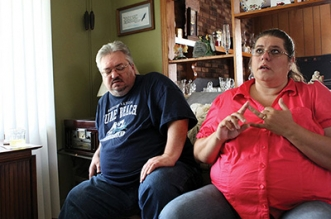 Constant Distress — Karen Turner recounts medical and other expenses the couple incurs while her husband David shifts to find a comfortable position to sit. (Photo by Ricky Leung)