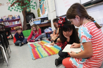 """Uncertain future — Second graders Taylor Eatman (right) and Karyme Mendoza read together during a """"buddy reading"""" time. Budget cuts have left teachers like Carter worried about how they will meet their students' needs with limited resources. (Photo by Ricky Leung)"""